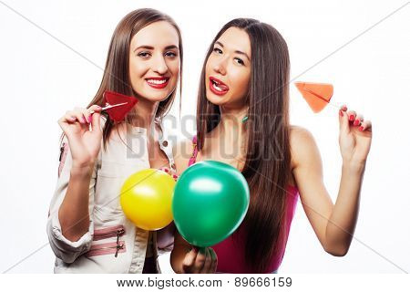 Two happy girls smiling and holding colored balloons and candys