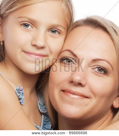 Portrait of a joyful mother and her daughter smiling at the camera. Studio shot.