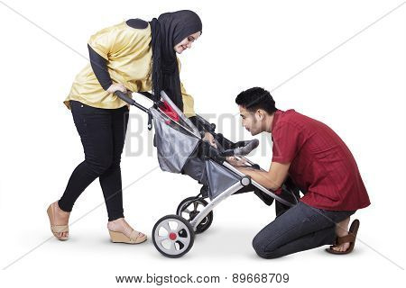 Happy Parents With Baby In The Perambulator