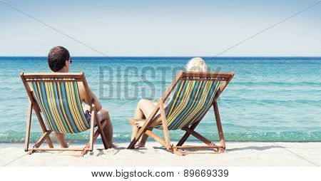 Young couple sitting in a beach chairs and looking at the sea