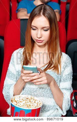 Girl texting sms in cinema