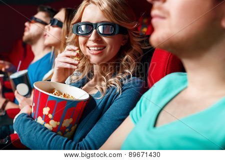 Woman in 3 d glasses eating popcorn.