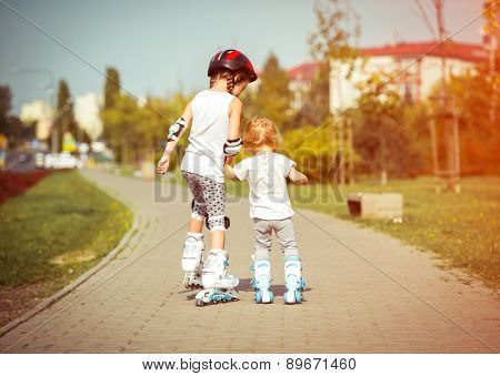 two little sisters to roller skate on the street, back view