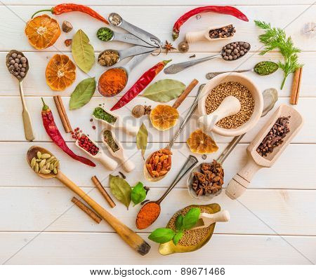 Collection of herbs and spices on a wooden background with heart-shaped