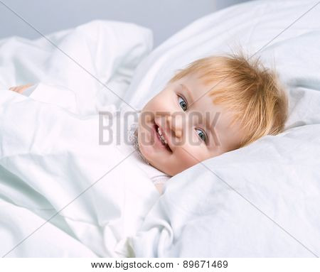 beautiful baby lying in a white bed and smiling