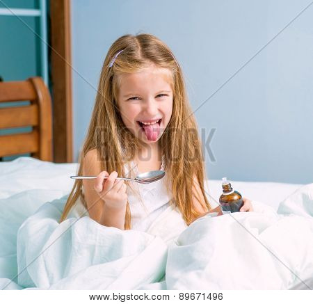 dissatisfied  little girl with influenza in bed, holding a cough syrup bottle