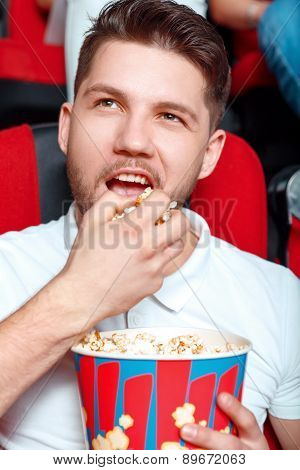 Man greedy eating popcorn in cinema.