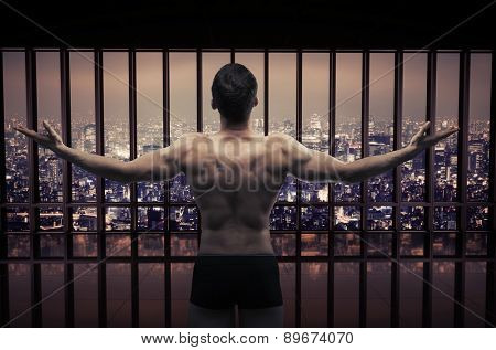 Young muscular athlete over night city view