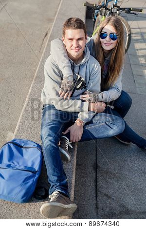 beautiful young  woman and young man with bike in the city