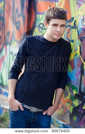 Attractive young blond man standing against colorful graffiti wall