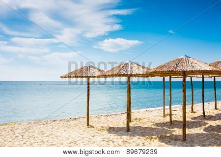 Row Of Wooden Umbrellas At Sandy Beach, Sea And Blue Sky