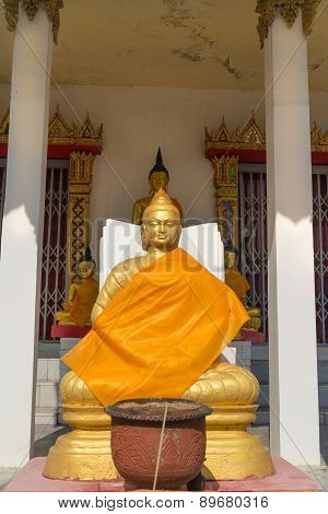 the gold buddha statue sitting  with incense burner