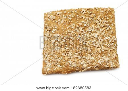 crispy spelt cracker with crushed wheat kernels on a white background