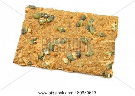 crispy spelt crackers with pumpkin seeds and cheese on a white background