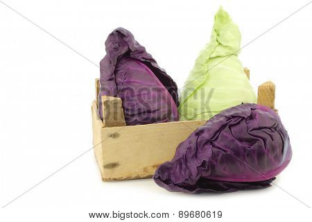 red and green pointed cabbage in a wooden crate on a white background