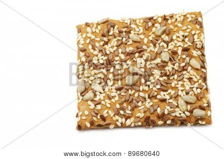 crispy spelt cracker with mixed seeds on a white background