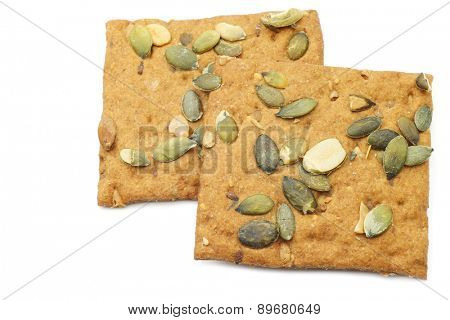 crispy spelt crackers with pumpkin seeds on a white background