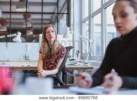 Young Woman Sitting At Her Desk Looking Away Thinking