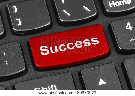 Computer notebook keyboard with Success key - technology background