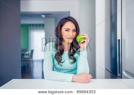 Portrait of a young woman with an apple inside a bright kitchen