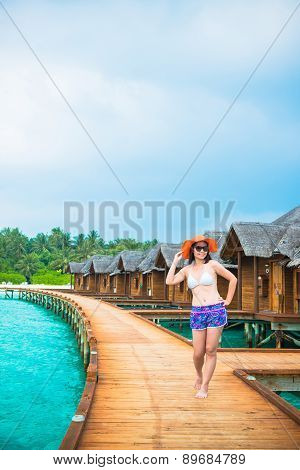 Woman is relaxing on the water bungalow of the tropical beach, Maldives