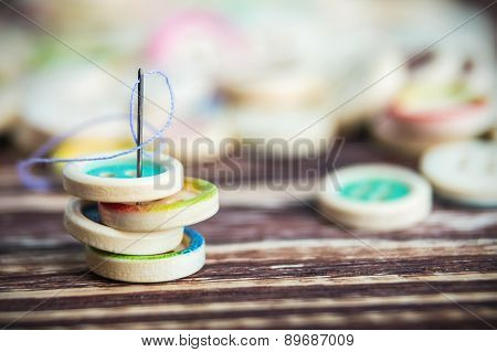 Stack Of Colorful Buttons With Sewing Needle