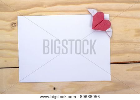 origami heart with wings over white paper sheet for love letter.