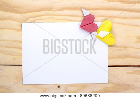 two origami hearts and white paper sheet for love message.