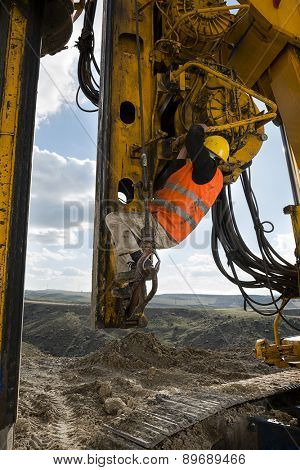 Construction worker climbing on drilling pile foundation.