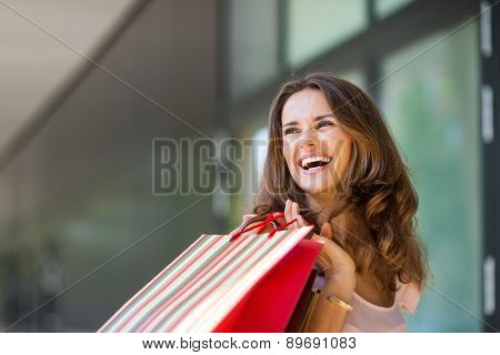 Happy Woman Out Shopping, Holding Up Colourful Shopping Bags