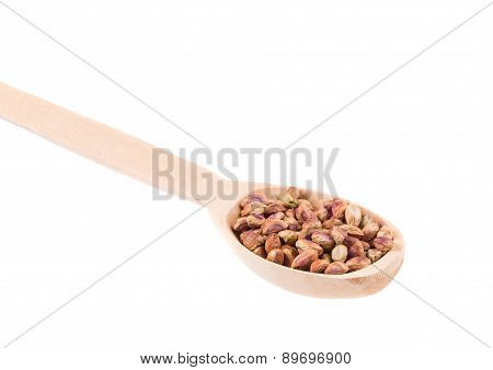 Wooden spoon with pistachios.