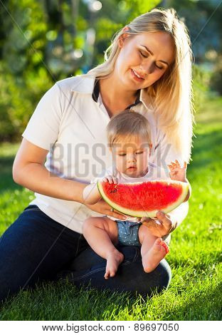 Young Happy Mother And Her Baby Daughter Eating Watermelon