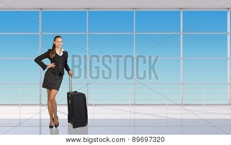 Smiling flight attendant standing with luggage