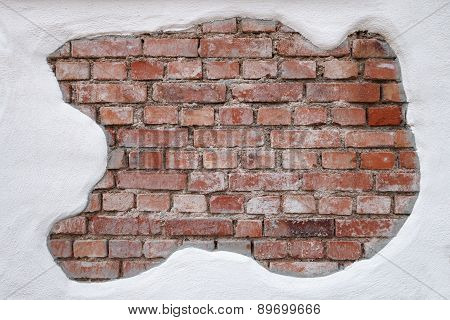 Partially plastered, old, dirty brick wall