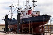 picture of shipyard  - Port side view of a fishing boat in a shipyard for maintenance - JPG