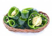 stock photo of poblano  - sliced poblano peppers on bamboo basket on white - JPG