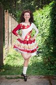 stock photo of wig  - Young woman in irish dance dress and wig dancing outdoor - JPG