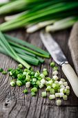 pic of scallion  - Chopped scallions on a rustic wooden board - JPG