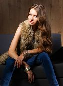 foto of vest  - Portrait of a elegant woman sitting on a black sofa wearing a blue jeans and fur vest - JPG