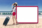 pic of carry-on luggage  - Young asian woman carrying a luggage standing near empty billboard at coast - JPG