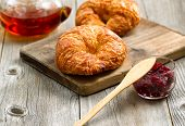 stock photo of croissant  - Fresh croissants focus on front of first croissant with fresh cranberry jam and tea for breakfast. Close up image with rustic wood underneath. ** Note: Shallow depth of field - JPG