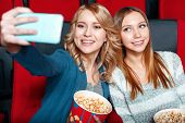 image of cinema auditorium  - Cinema selfie. Two beautiful smiling girls excited doing selsie in cinema with popcorn and coke.