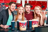 image of popcorn  - Full size popcorn. Group of young smiling people buying popcorn and  drinks before watching film in cinema