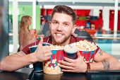 pic of popcorn  - Greedy man. Young smiling greedy man buying popcorn and drinks before watching film in cinema and showing class.