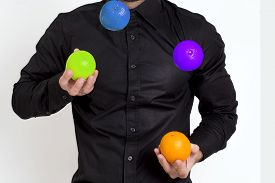picture of juggling  - Man in black shirt juggling with multicolored oranges - JPG
