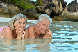 foto of wallow  - Elderly couple lying on the beach in the water - JPG