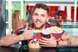 stock photo of cinema auditorium  - Greedy man. Young smiling greedy man buying popcorn and drinks before watching film in cinema and showing class. ** Note: Shallow depth of field - JPG