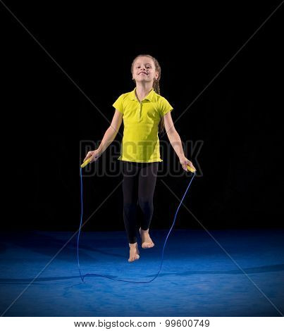 Little girl doing gymnastic exercises on black