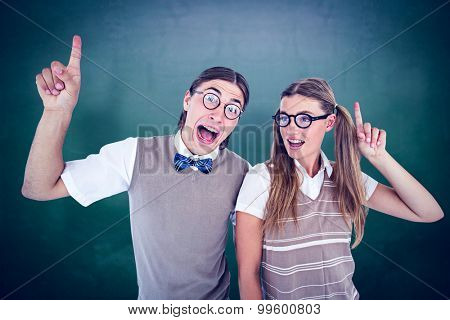 Geeky hipsters pointing against green chalkboard