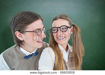 Geeky hipster couple smiling at each other against green chalkboard